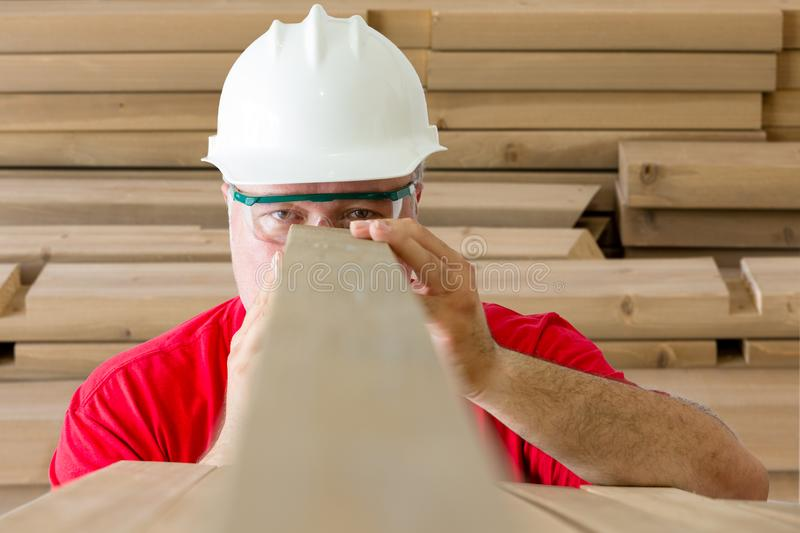 Worker inspecting quality of wooden plank stock images