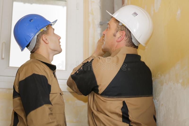 Worker inspecting the walls. Apprentice royalty free stock photography