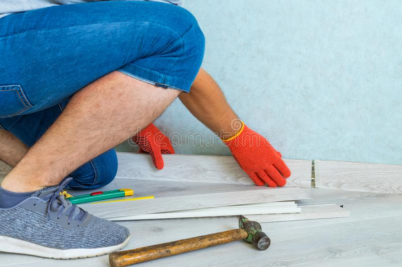 Worker instal plastic skirting board on laminate flooring. Renovation of baseboard at home. Worker instal plastic skirting board on laminate flooring royalty free stock images