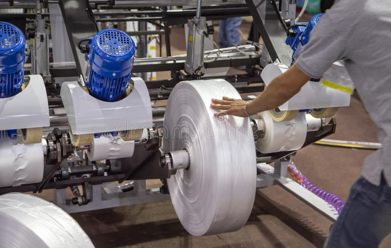 Worker install film roll for plastic bag extruder machine. Worker install film roll for extruder machine of polyethylene for industry process of plastic bag royalty free stock image