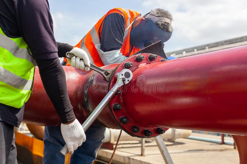 Worker install Tightening bolts & Nuts of piping Flange system. In the industrial plant stock images
