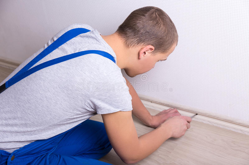 Worker installing baseboard at the bottom of the wall. Worker in unifor installing baseboard at the bottom of the wall royalty free stock images