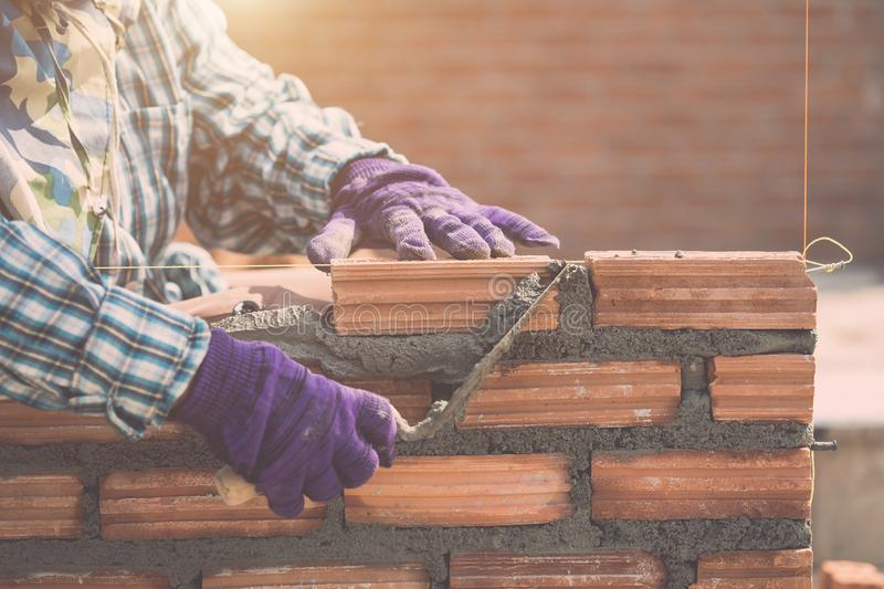 Worker installing bricks wall in process of house building stock photos