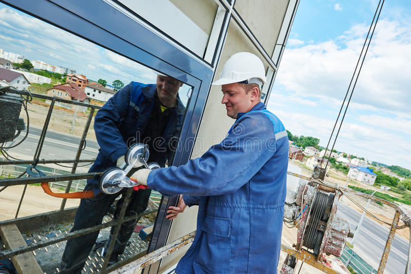 Worker installing facade window. Window installation. male industrial builder worker at facade glazing royalty free stock photo