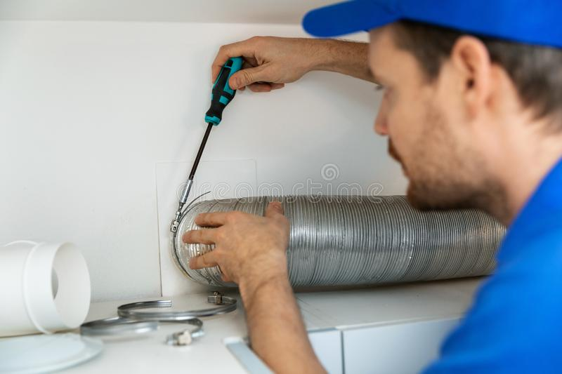 Worker installing flexible aluminum ventilation tube for kitchen cooker hood. Exhaust system stock images