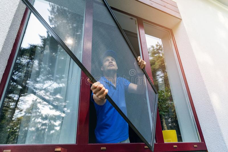 Worker installing mosquito net wire screen on plastic window royalty free stock photo