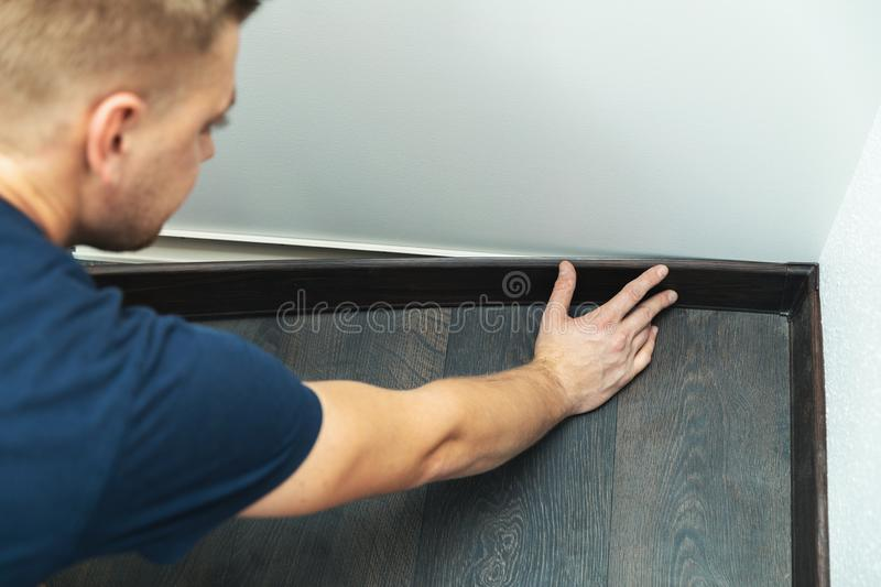Worker installing plastic baseboard. On the laminate floor royalty free stock photography