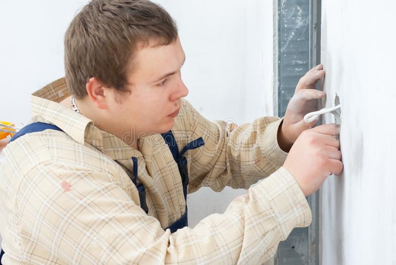 Worker installing power socket in wall stock photography