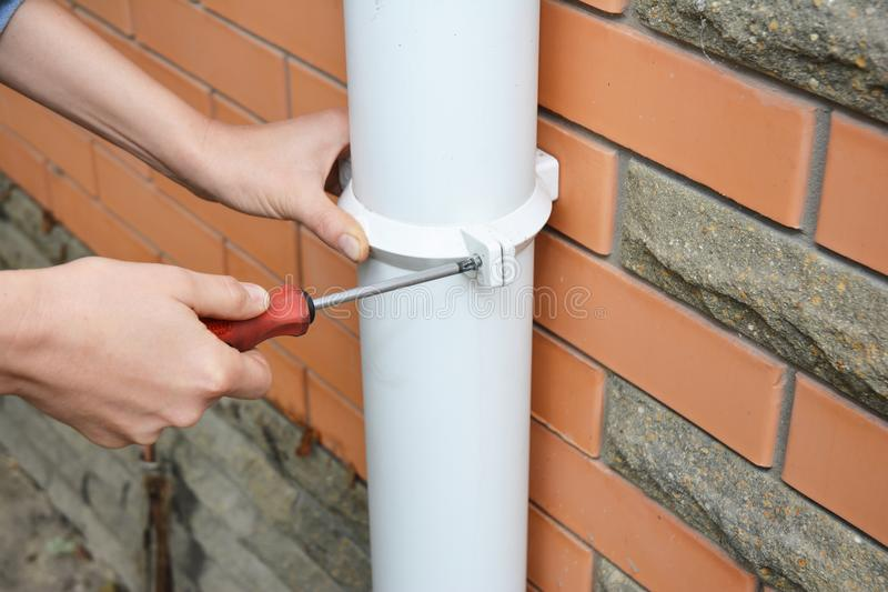 Worker Installing rain gutter downpipe. Contractor hands repair rain gutter downspout pipe with screwdriver. Guttering, Gutters, royalty free stock image