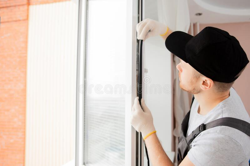 Worker in installing rubber seals on plastic upvc window royalty free stock images