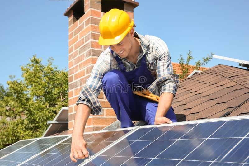 Worker installing solar panels royalty free stock image