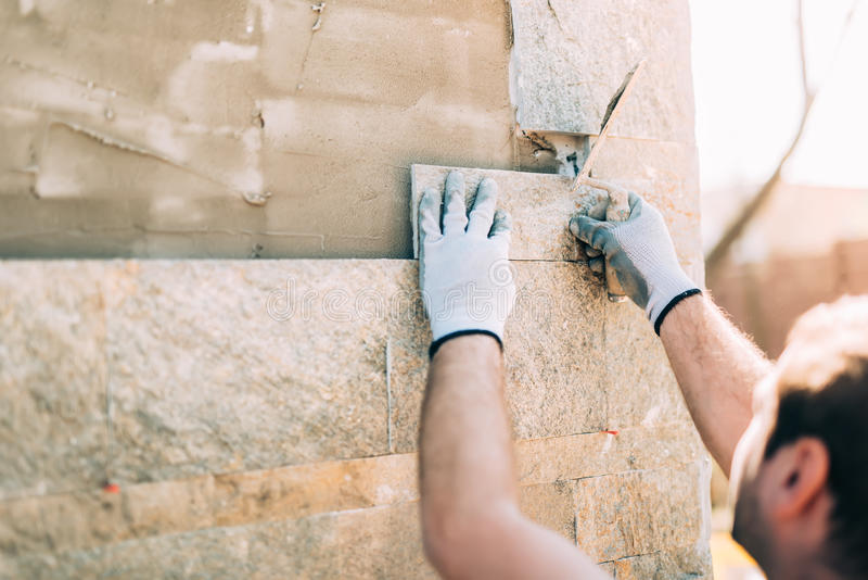 Worker installing stone tiles on wall on construction site royalty free stock image
