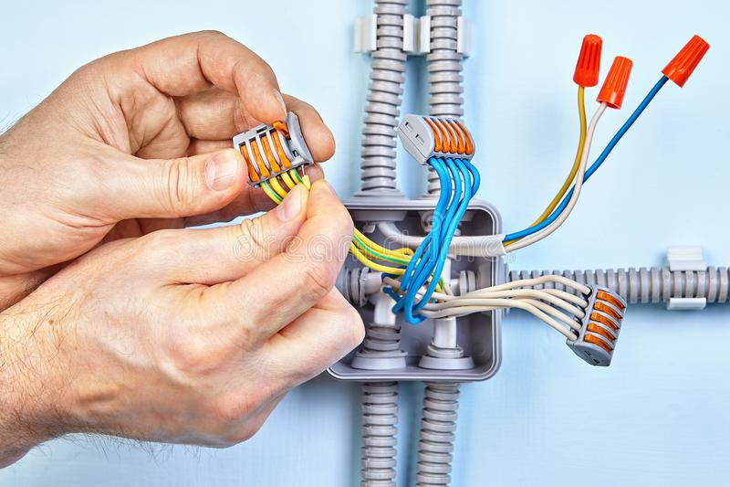Worker is installing surface mounted wiring. Electrician is making new junction box for electrical wires with help of push wire connectors and closed end crimp royalty free stock photo