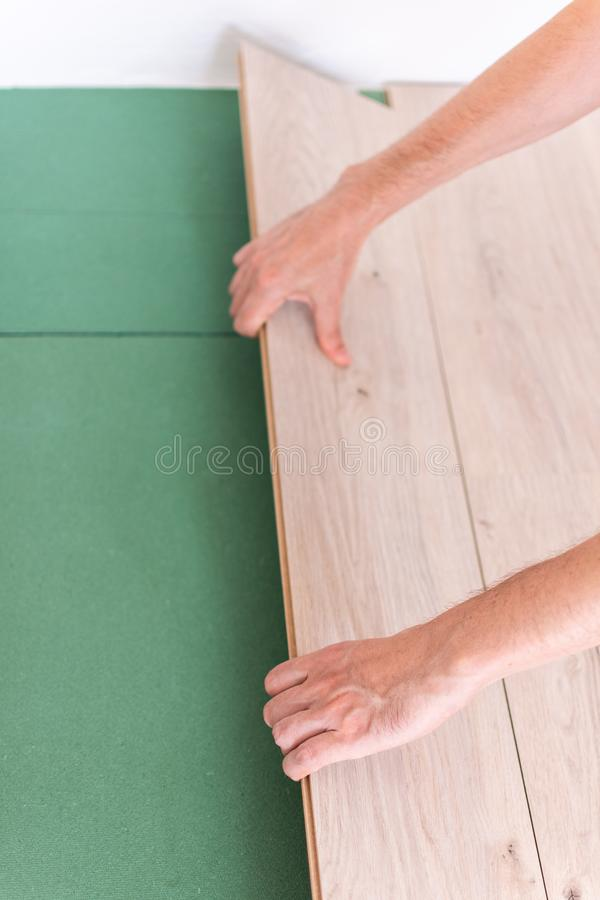 Worker installing wooden laminate flooring royalty free stock photo