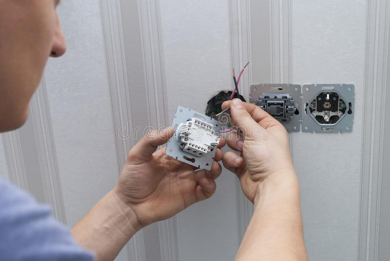 Electrician installs lighting switch stock photography