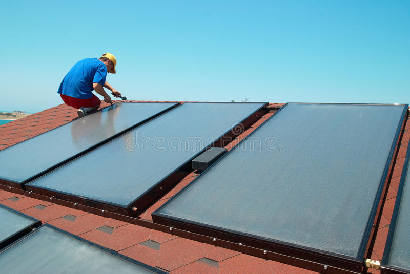 Worker installs solar panels. Worker solar water heating panels on the roof stock images