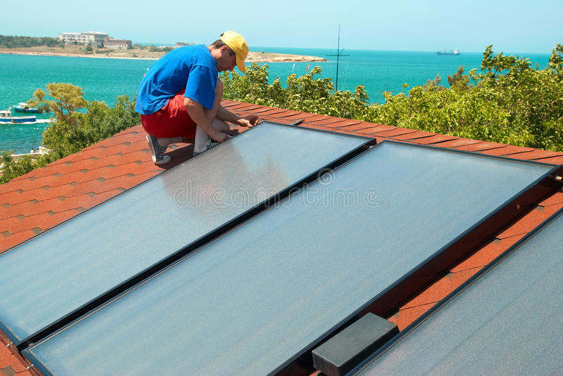 Worker installs solar panels. Worker solar water heating panels on the roof stock photos