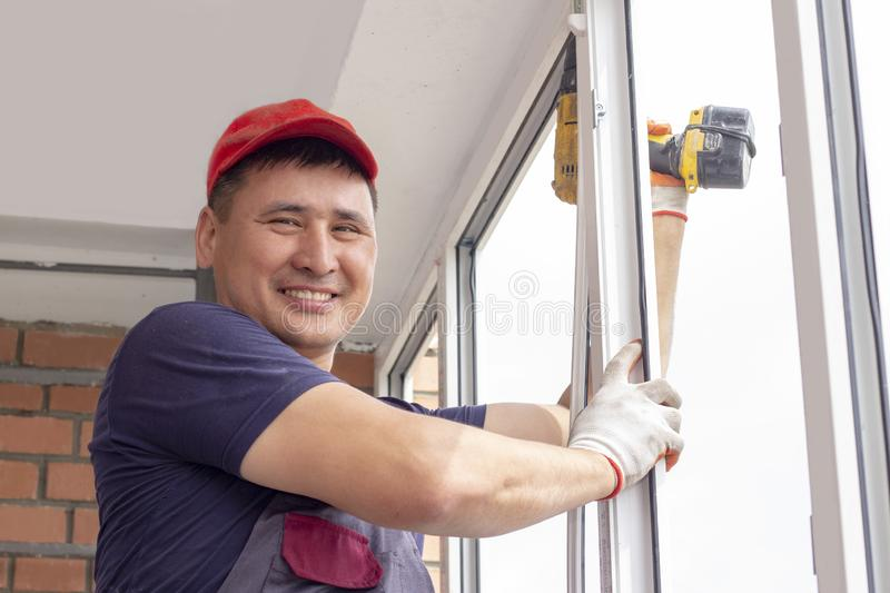 Worker installs window master sverdit frame to attach to  base repair in high-rise building royalty free stock photo