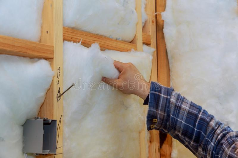 Worker in insulating rock wool insulation in wooden frame for future house walls for warm home. Worker in insulating rock wool insulation in wooden frame for stock images