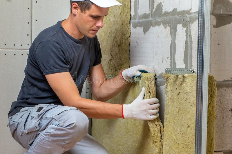 Worker insulating a room wall with mineral rock wool thermal insulation stock image