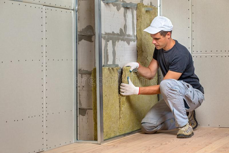 Worker insulating a room wall with mineral rock wool thermal insulation royalty free stock photography