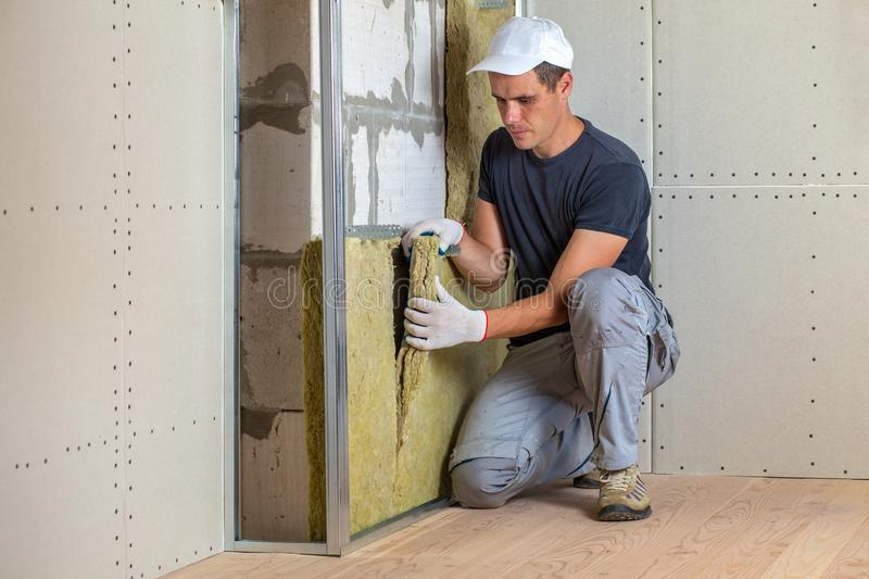 Worker insulating a room wall with mineral rock wool thermal insulation stock photography