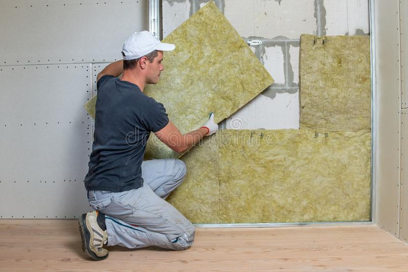 Worker insulating a room wall with mineral rock wool thermal insulation royalty free stock photo