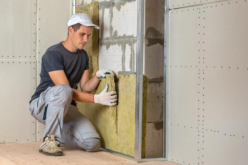 Worker insulating a room wall with mineral rock wool thermal insulation stock photo