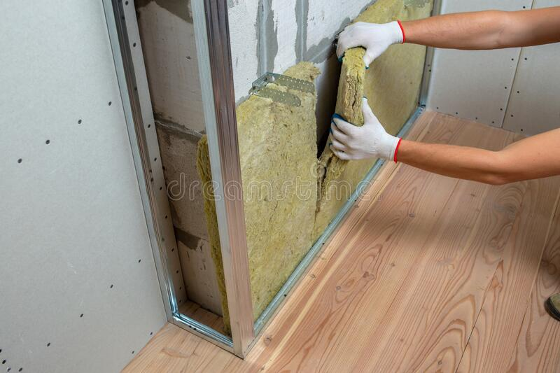 Worker insulating a room wall with mineral rock wool thermal insulation stock images