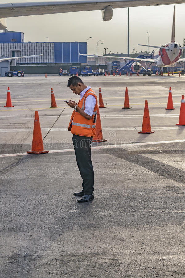 Worker at Jorge Chavez Airport, Lima, Peru. LIMA, PERU, APRIL - 2016 - Worker watching his cellphone at Jorge Chavez airport runway in Lima city, Peru stock image