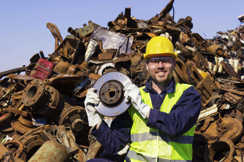 Worker on junkyard hold rotor like shiny trophy. Copy space available royalty free stock photography