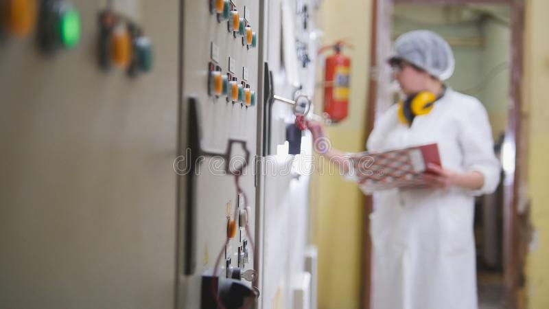 Worker in lab coat at the food factory. De-focused royalty free stock photography