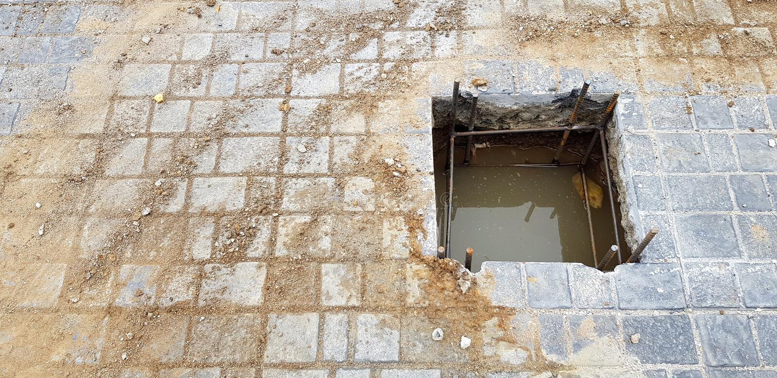 Worker or labor digging hole for installation pillar or pole on cement ground with copy space at construction site stock image