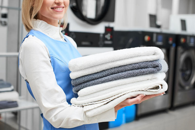 Worker Laundry girl holding fresh towels in her hands and smiles stock images