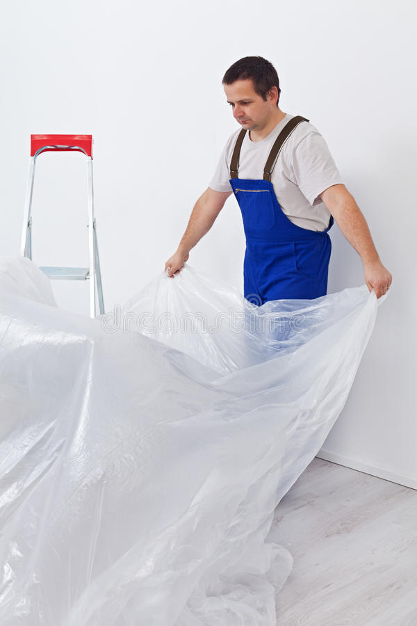Worker Laying Down Thin Protective Foil Before Painting Royalty Free Stock Photo