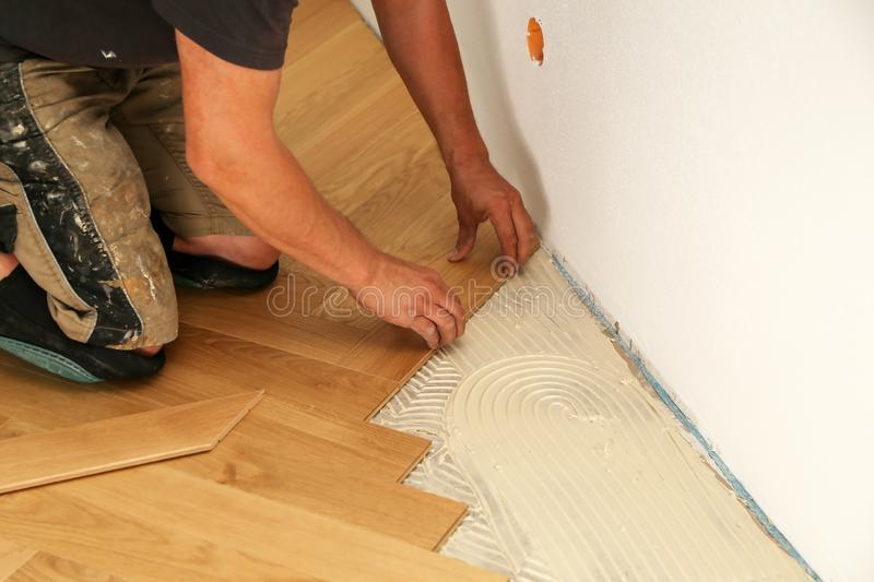 Worker laying parquet flooring. Worker installing wooden laminate flooring stock photos