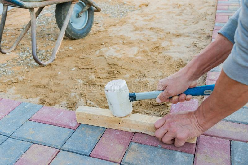 Worker laying red and gray concrete paving blocks. Road Paving, construction royalty free stock images