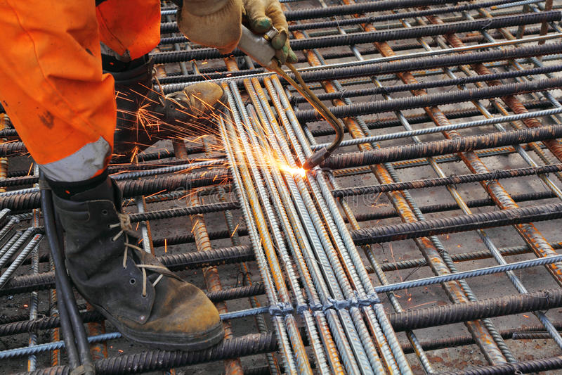 Worker legs weld metal grating. Worker legs in orange clothes weld metal grating by acetylene torch stock image
