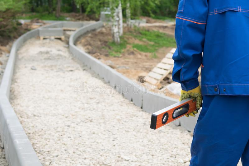 A worker with a level to measure the slope is on the road that is being built, rear view stock photo