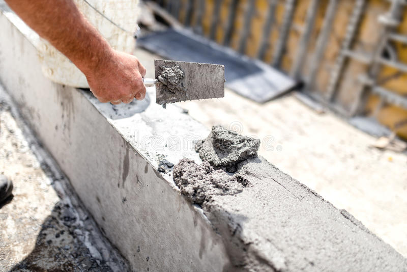 Worker leveling concrete with putty knife at building site. Details of construction industry royalty free stock image