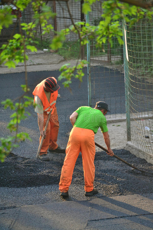 Worker leveling fresh asphalt stock photos