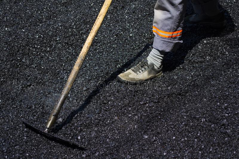 Worker leveling fresh asphalt on a road construction site, indus royalty free stock images