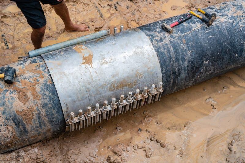 Worker lock Cast aluminium cover & PVC Plastic water pipe broken, 600 mm. diameter band with torque bolt screw. Water PVC Plastic stock image