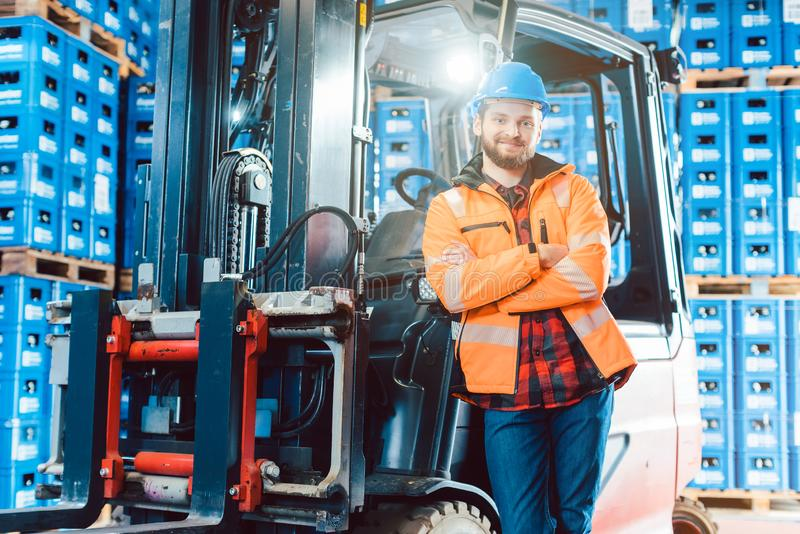 Worker in logistics distribution center with his forklift. Worker in logistics distribution center leaning against his forklift royalty free stock photo