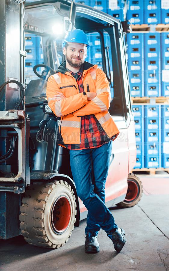 Worker in logistics distribution center with his forklift. Worker in logistics distribution center leaning against his forklift stock image