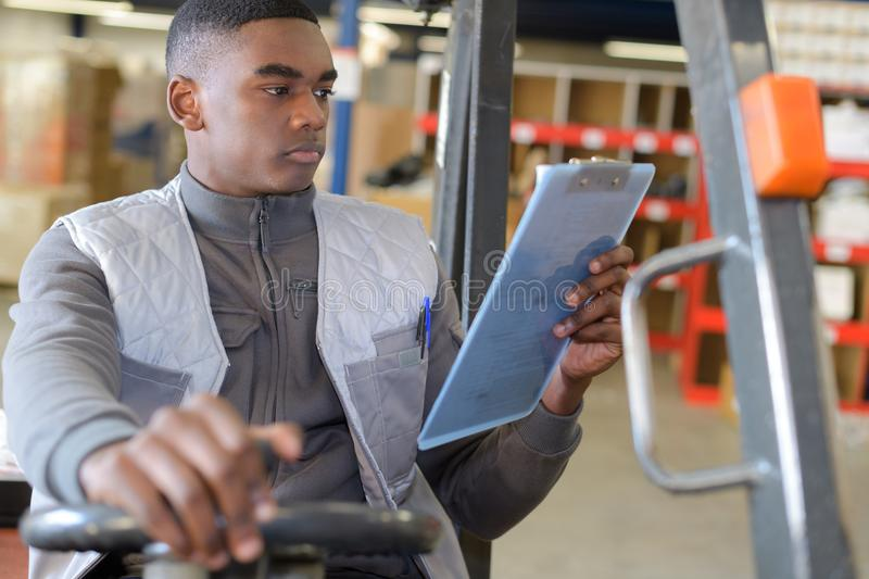 Worker in logistics warehouse using forklift checking list. Worker in logistics warehouse using a forklift checking list royalty free stock photo