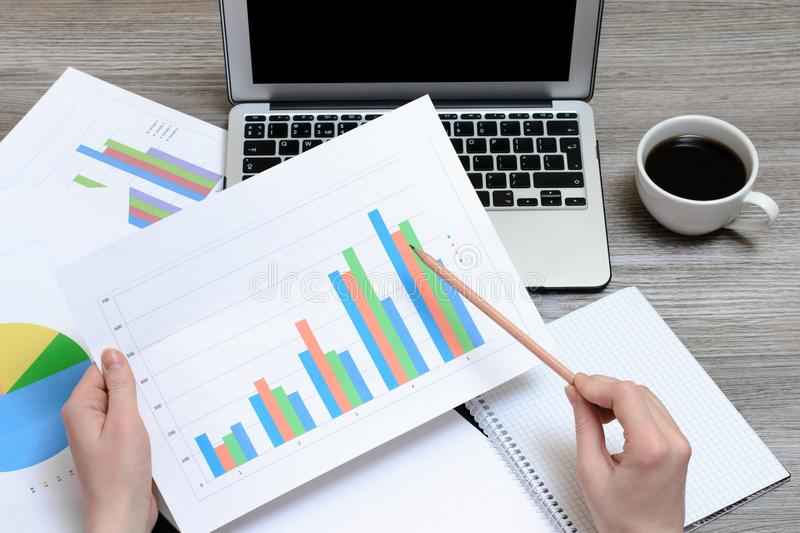 Worker looking at graphics. Top view on hands holding graphs, laptop, cup of coffee, workplace workstation, project progress best royalty free stock photo