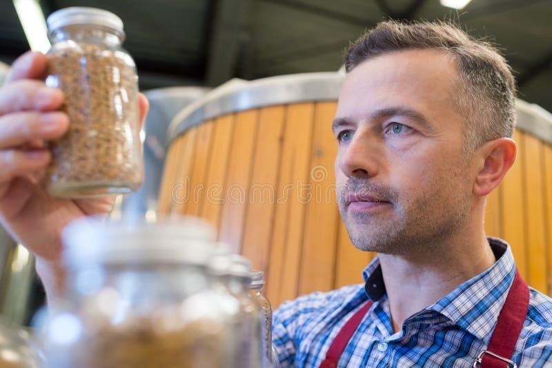 Worker looking at ingredient in glass jar stock image