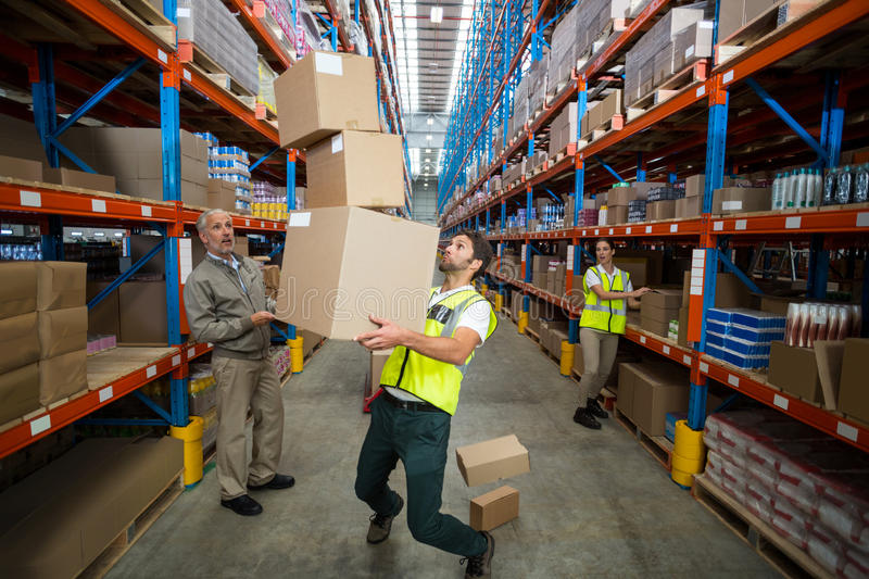 Worker losing his balance while carrying cardboard boxes stock images