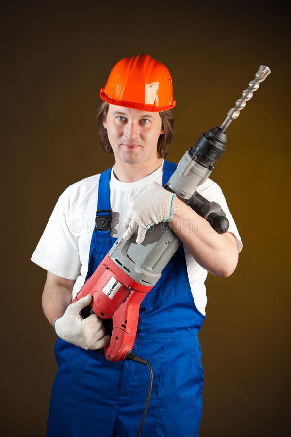 Worker with a machine drill. Worker holding a machine drill stock photo